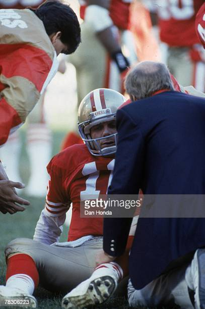 Quarterback Joe Montana of the San Francisco 49ers is tended to by the medical staff after taking a hit against the New York Giants in the 1990 NFC...