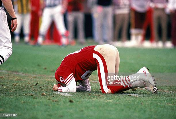 Quarterback Joe Montana of the San Francisco 49ers lies on the ground after being hit during the 1990 NFC Divisional Playoff Game against the...