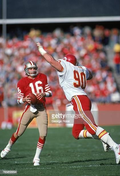 Quarterback Joe Montana of the San Francisco 49ers looks to pass while under pressure from Kansas City Chiefs defensive end Bob Hamm during a game at...