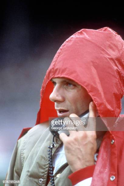 Quarterback Joe Montana of the San Francisco 49ers takes cover from the rain while talking on the phone to coaches who were stationed overhead in the...