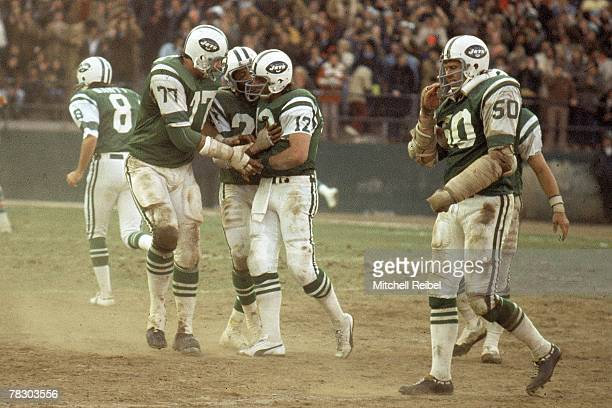 Quarterback Joe Namath of the New York Jets is mobbed by his teammates after throwing a touchdown pass during a 1714 victory over the Miami Dolphins...