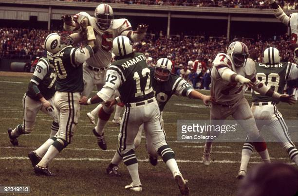 Quarterback Joe Namath of the New York Jets throws a pass during a game while under pressure from defensive lineman Arthur Moore and Mel Lunsford of...