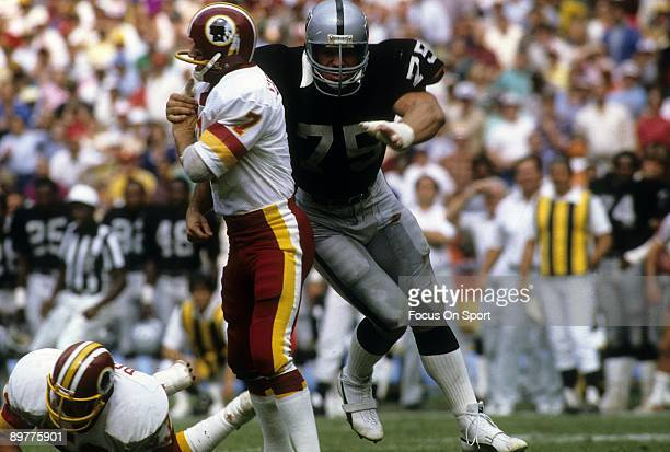 Quarterback Joe Theismann of the Washington Redskins gets his pass off before getting hit by defensive tackle Howie Long of the Los Angeles Raiders...