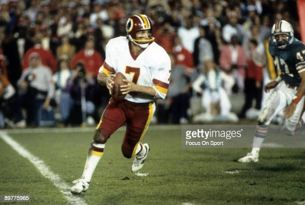 Quarterback Joe Theismann of the Washington Redskins in action rolls out with the ball against the Miami Dolphins during Super Bowl XVII on January...