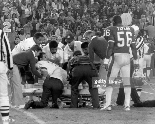 Quarterback Joe Theismann of the Washington Redskins is carted off the field by medical staff after having his leg broken by Giants defensive end...
