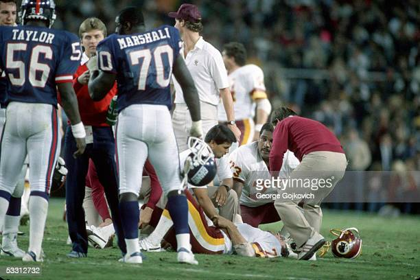 Quarterback Joe Theismann of the Washington Redskins is helped by teammate Mark May and others after being injured when sacked by linebacker Lawrence...
