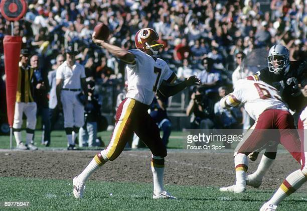 Quarterback Joe Theismann of the Washington Redskins throw a pass against the Los Angeles Raiders during a 1983 NFL football game at RFK Stadium in...