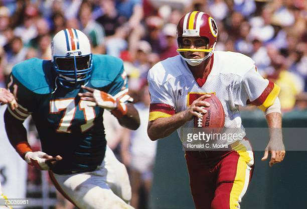 Quarterback Joe Theismann scrambes during a game against the Miami Dolphins on September 2 1984 in Washington District of Columbia