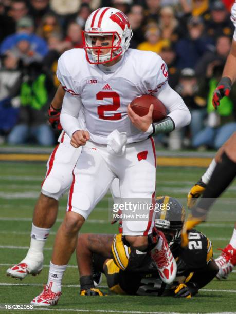 Quarterback Joel Stave of the Wisconsin Badgers breaks a tackle during the second quarter by linebacker Christian Kirksey of the Iowa Hawkeyes on...