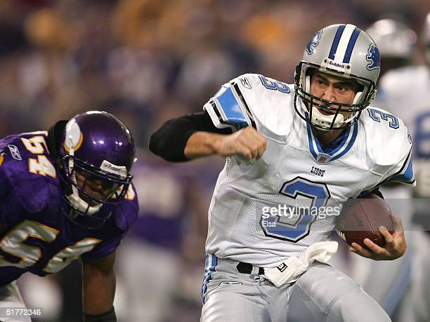 Quarterback Joey Harrington of the Detroit Lions scrambles as he is chased by Dontarrious Thomas of the Minnesota Vikings on November 21 2004 at the...
