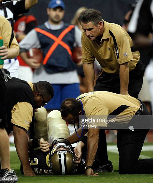 Quarterback Joey Harrington of the New Orleans Saints is helped by medical staff after taking a hard hit on August 22 2009 in Houston Texas