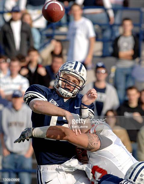 BYU quarterback John Beck just gets the pass away as New Mexico defensive lineman Wesley Beck applies the hit to Beck during the second quarter at...