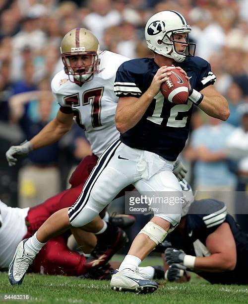 Quarterback John Beck of the Brigham Young Cougars looks to pass the ball as defensive end Nick Larkin of the Boston College Eagles moves in on...
