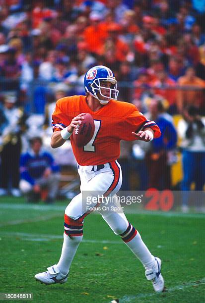 Quarterback John Elway of the Denver Broncos drops back to pass against the Dallas Cowboys during an NFL football game October 5 1986 at Mile High...