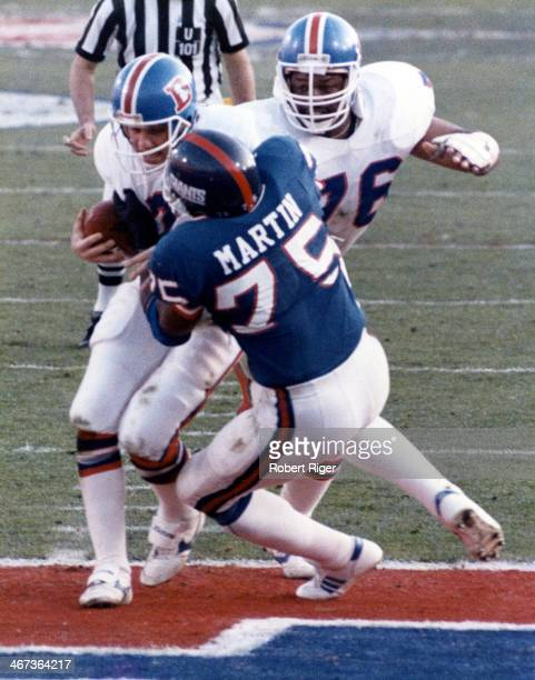 Quarterback John Elway of the Denver Broncos is sacked by George Martin of the New York Giants scoring a safety during Super Bowl XXI on January 25...