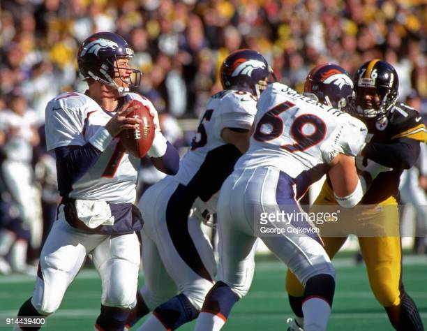 Quarterback John Elway of the Denver Broncos looks to pass as offensive linemen Gary Zimmerman and Mark Schlereth block against defensive lineman...