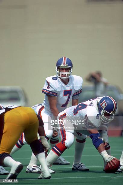 Quarterback John Elway of the Denver Broncos prepares to take the ball from center during his NFL debut in a game against the Pittsburgh Steelers at...