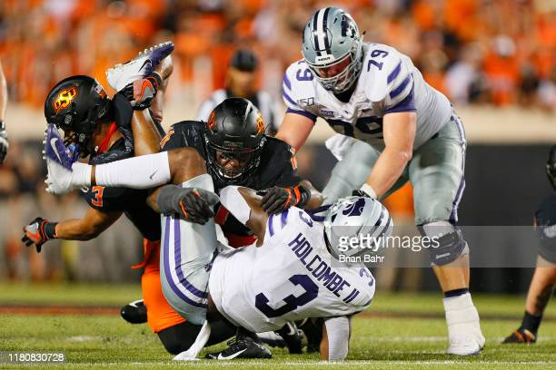 Quarterback John Holcombe II of the Kansas State Wildcats gets wrapped up by linebacker Amen Ogbongbemiga and safety Tre Sterling of the Oklahoma...