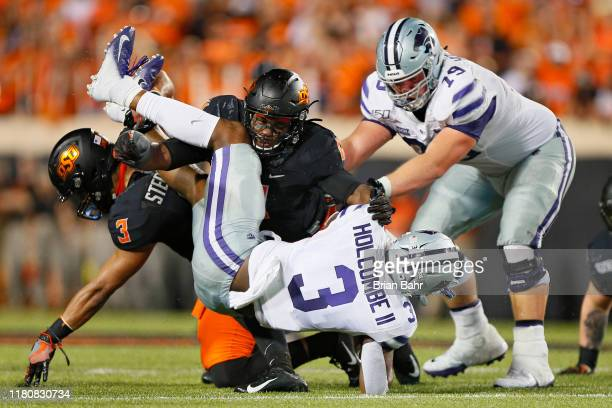 Quarterback John Holcombe II of the Kansas State Wildcats gets flipped up by linebacker Amen Ogbongbemiga and safety Tre Sterling of the Oklahoma...