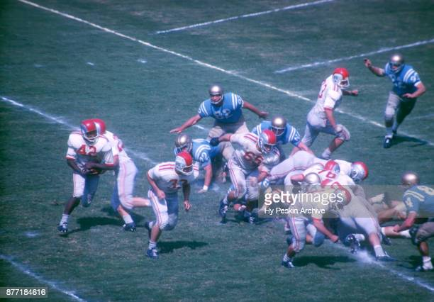 Quarterback John Mummey of the Ohio State Buckeyes hands the ball off to Paul Warfield as David Francis blocks during an NCAA game against the UCLA...