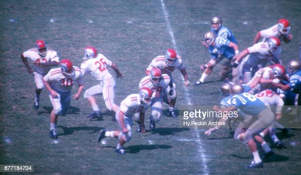 Quarterback John Mummey of the Ohio State Buckeyes hands the ball off to Paul Warfield as David Katterheinrich blocks during an NCAA game against the...