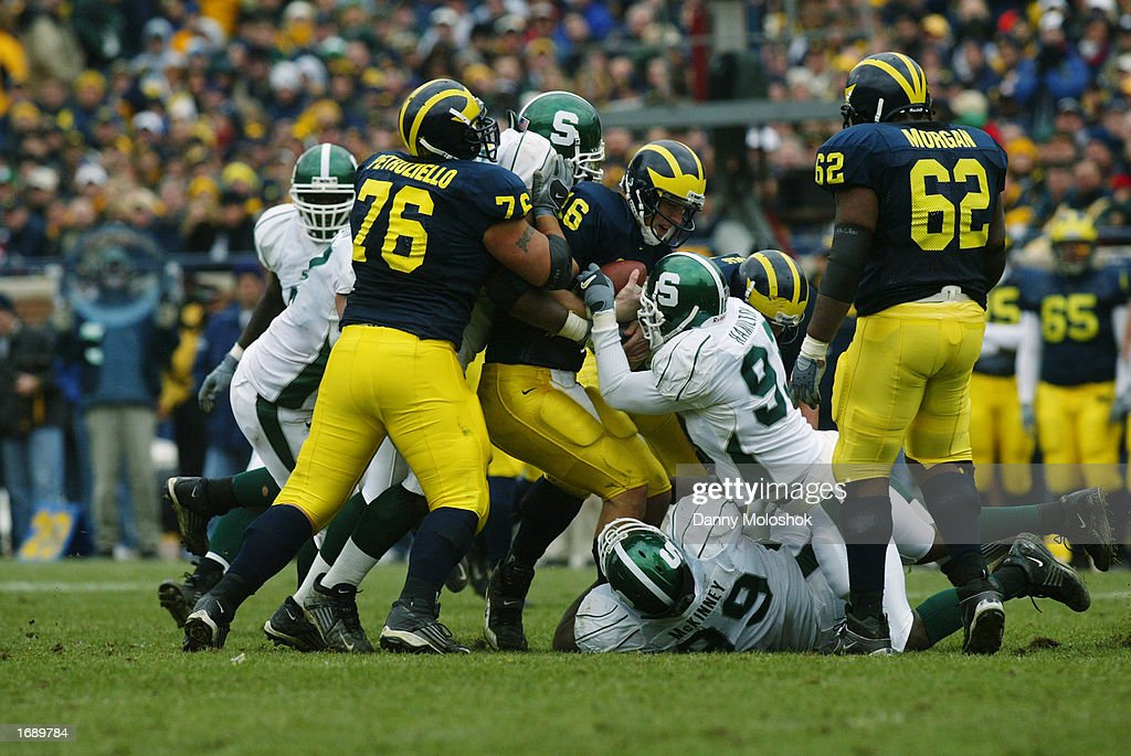Quarterback John Navarre #16 of the Michigan Wolverines is tackled by the Michigan State Spartans defense during the game on November 2, 2002 at Michigan Stadium in Ann Arbor, Michigan. Michigan won 49-3.