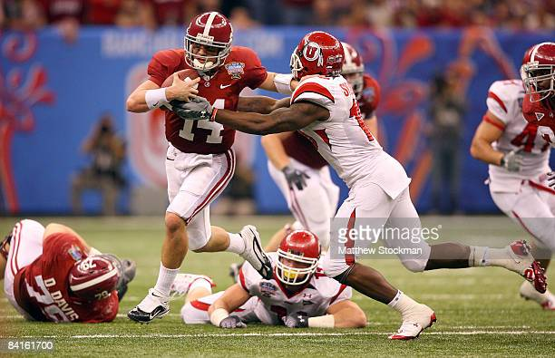 Quarterback John Parker Wilson of the Alabama Crimson Tide looks to avoid a tackle by linebacker Stevenson Sylvester of the Utah Utes in the second...