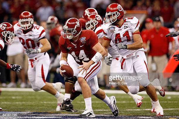Quarterback John Parker Wilson of the Alabama Crimson Tide runs as he is chased by defensive lineman Koa Misi of the Utah Utes in the second half...