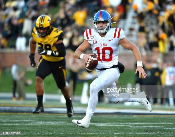 Quarterback John Rhys Plumlee of the Mississippi Rebels looks for an open receiver as gets past defensive lineman Chris Turner of the Missouri Tigers...