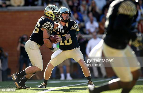 Quarterback John Wolford of the Wake Forest Demon Deacons hands off to running back Cade Carney during the first quarter of an NCAA football game...