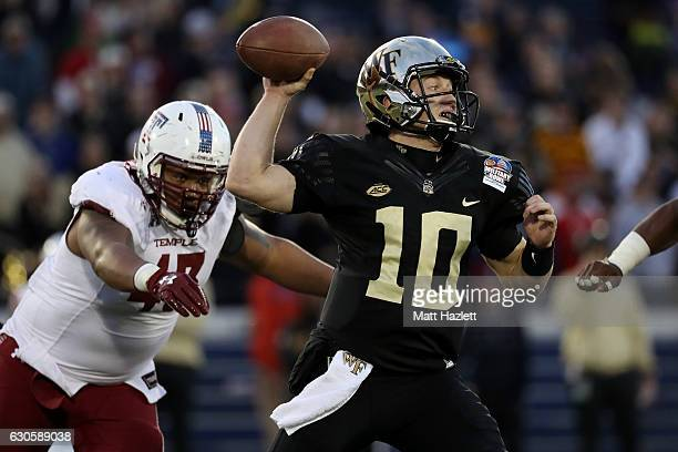 Quarterback John Wolford of the Wake Forest Demon Deacons passes the ball while under pressure from defensive lineman Averee Robinson of the Temple...