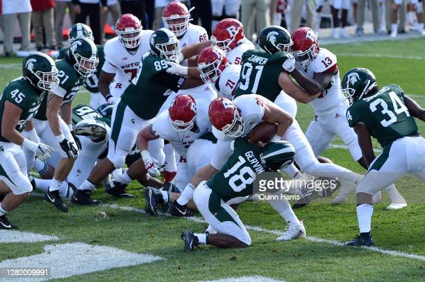 Quarterback Johnny Langan of the Rutgers Scarlet Knights runs through cornerback Kalon Gervin of the Michigan State Spartans to score a touchdown in...