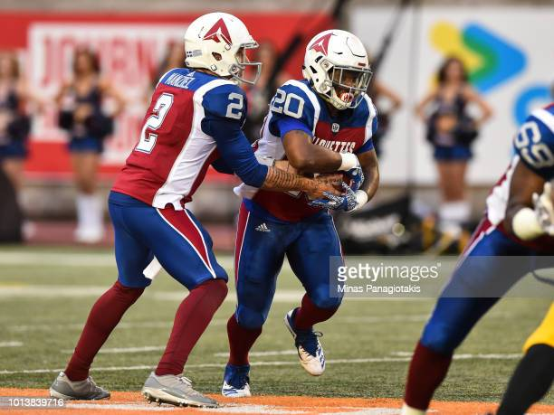 Quarterback Johnny Manziel hands off the ball to running back Tyrell Sutton of the Montreal Alouettes against the Hamilton TigerCats during the CFL...