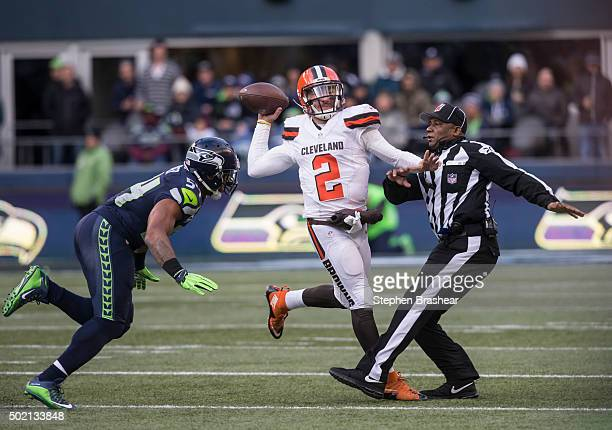 Quarterback Johnny Manziel of the Cleveland Browns passes the ball as he runs into umpire Barry Anderson, right, while linebacker Bobby Wagner of the...