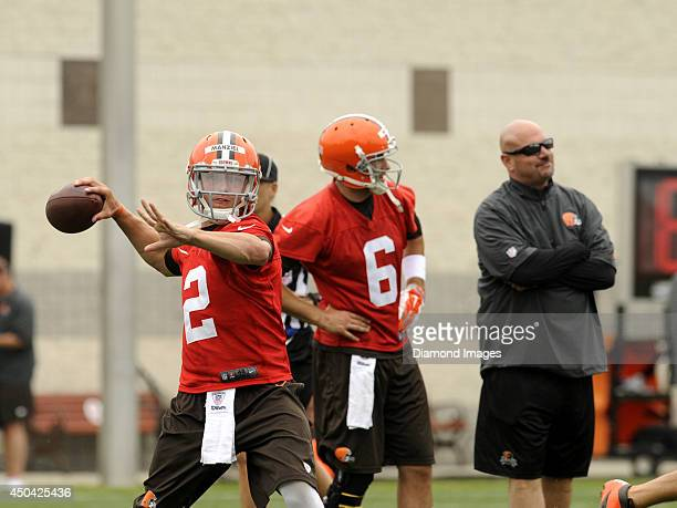 Quarterback Johnny Manziel of the Cleveland Browns throws a pass while quarterback Brian Hoyer and head coach Mike Pettine watch a drill during a...