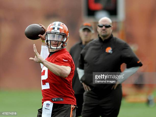 Quarterback Johnny Manziel of the Cleveland Browns throws a pass while head coach Mike Pettine and his father Mike Sr watch from behind during a mini...