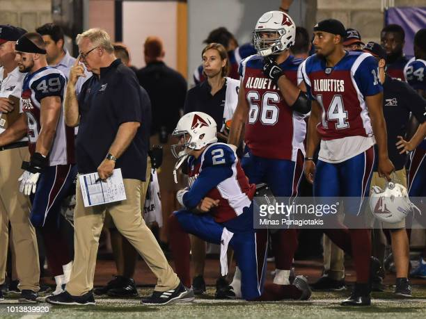 Quarterback Johnny Manziel of the Montreal Alouettes is on one knee while his teammates and head coach Mike Sherman walk off the field against the...