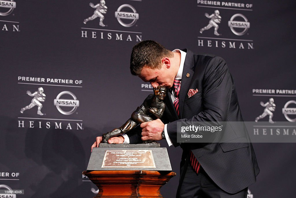 Quarterback Johnny Manziel of the Texas A&M University Aggies kisses the Heisman Memorial Trophy after being named the 78th Heisman Memorial Trophy Award winner at a press conference after the 78th Heisman Trophy Presentation at the Marriott Marquis on December 8, 2012 in New York City.