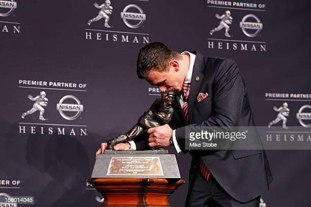 Quarterback Johnny Manziel of the Texas AM University Aggies kisses the Heisman Memorial Trophy after being named the 78th Heisman Memorial Trophy...