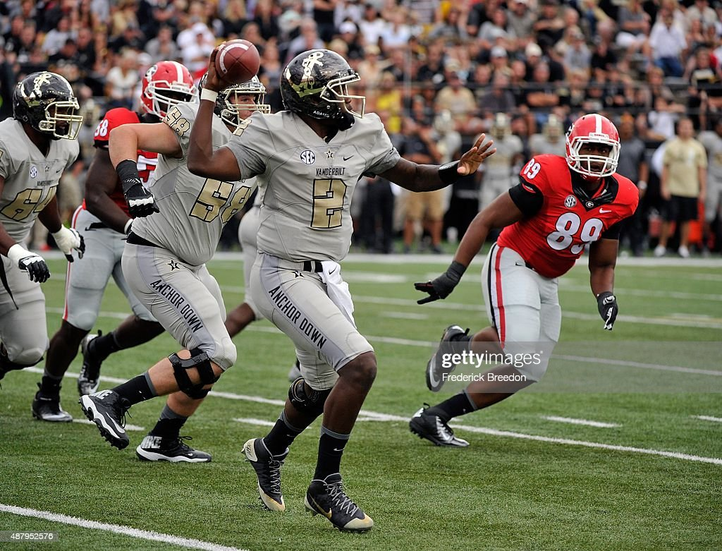 Quarterback Johnny McCrary #2 of the Vanderbilt Commodores rolls out of the pocket to throw a pass against James DeLoach #89 of the Georgia Bulldogs during the first half at Vanderbilt Stadium on September 12, 2015 in Nashville, Tennessee.