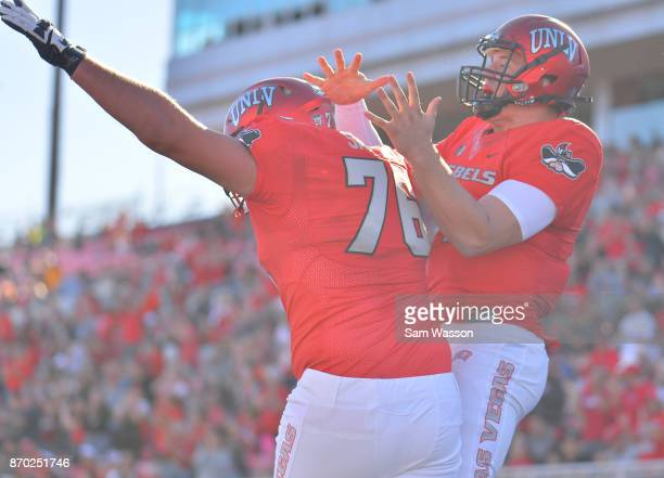 Quarterback Johnny Stanton and offensive lineman Kyle Saxelid of the UNLV Rebels celebrate after Stanton scored a touchdown during their game against...