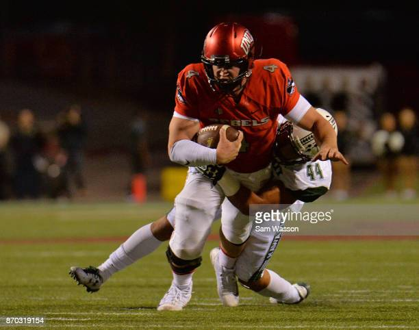 Quarterback Johnny Stanton of the UNLV Rebels is tackled by linebacker Russell Williams Jr #44 of the Hawaii Warriors during their game at Sam Boyd...