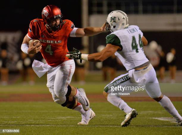 Quarterback Johnny Stanton of the UNLV Rebels stiff arms linebacker Russell Williams Jr #44 of the Hawaii Warriors during their game at Sam Boyd...