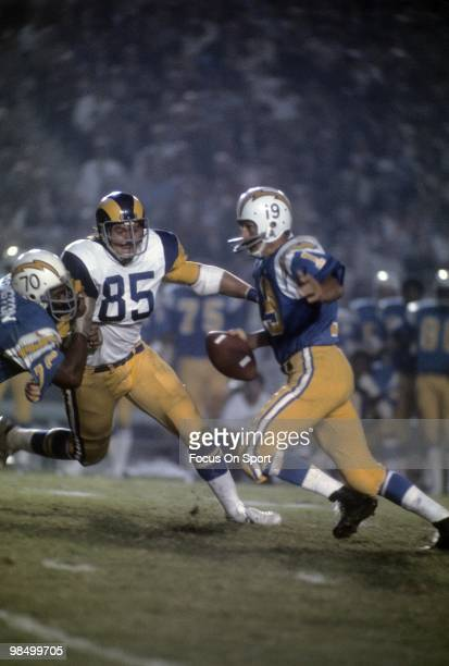Quarterback Johnny Unitas of the San Diego Charger scrambles away from defensive end Jack Youngblood of the Los Angeles Rams circar 1973 during an...