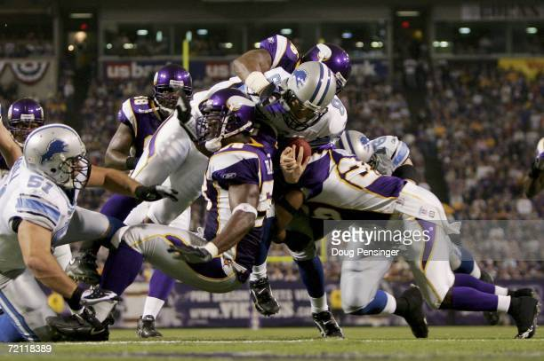 Quarterback Jon Kitna of the Detroit Lions collides with Antoine Winfield and Napoleon Harris of the Minnesota Vikings defense as he scores on an...