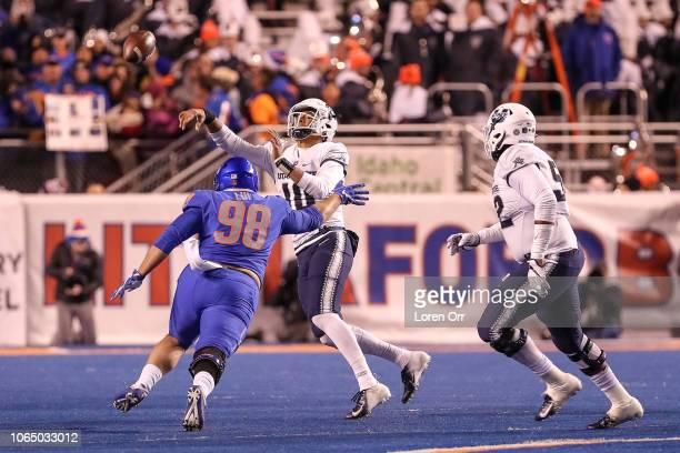 Quarterback Jordan Love of the Utah State Aggies gets a pass away while being pressured by nose tackle Sonatane Lui of the Boise State Broncos during...