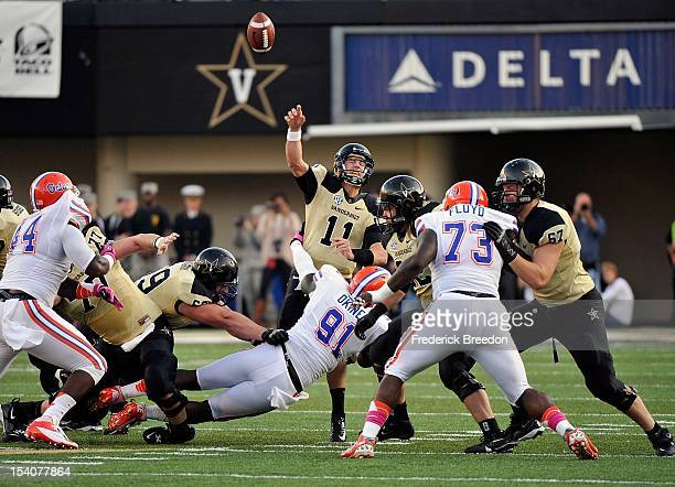 Quarterback Jordan Rodgers of the Vanderbilt Commodores gets hit by Earl Okine of the Florida Gators as he releases a pass at Vanderbilt Stadium on...