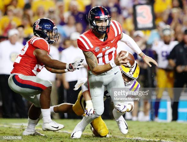 Quarterback Jordan Ta'amu of the Mississippi Rebels runs the ball under pressure during the third quarter against the LSU Tigers at Tiger Stadium on...