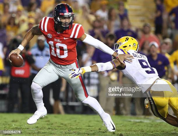 Quarterback Jordan Ta'amu of the Mississippi Rebels runs the ball under pressure from safety Grant Delpit of the LSU Tigers during the third quarter...