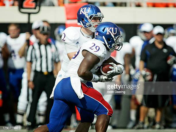Quarterback Jordan Webb hands off to running back James Sims of Kansas in the first half against Oklahoma State October 8 2011 at Boone Pickens...